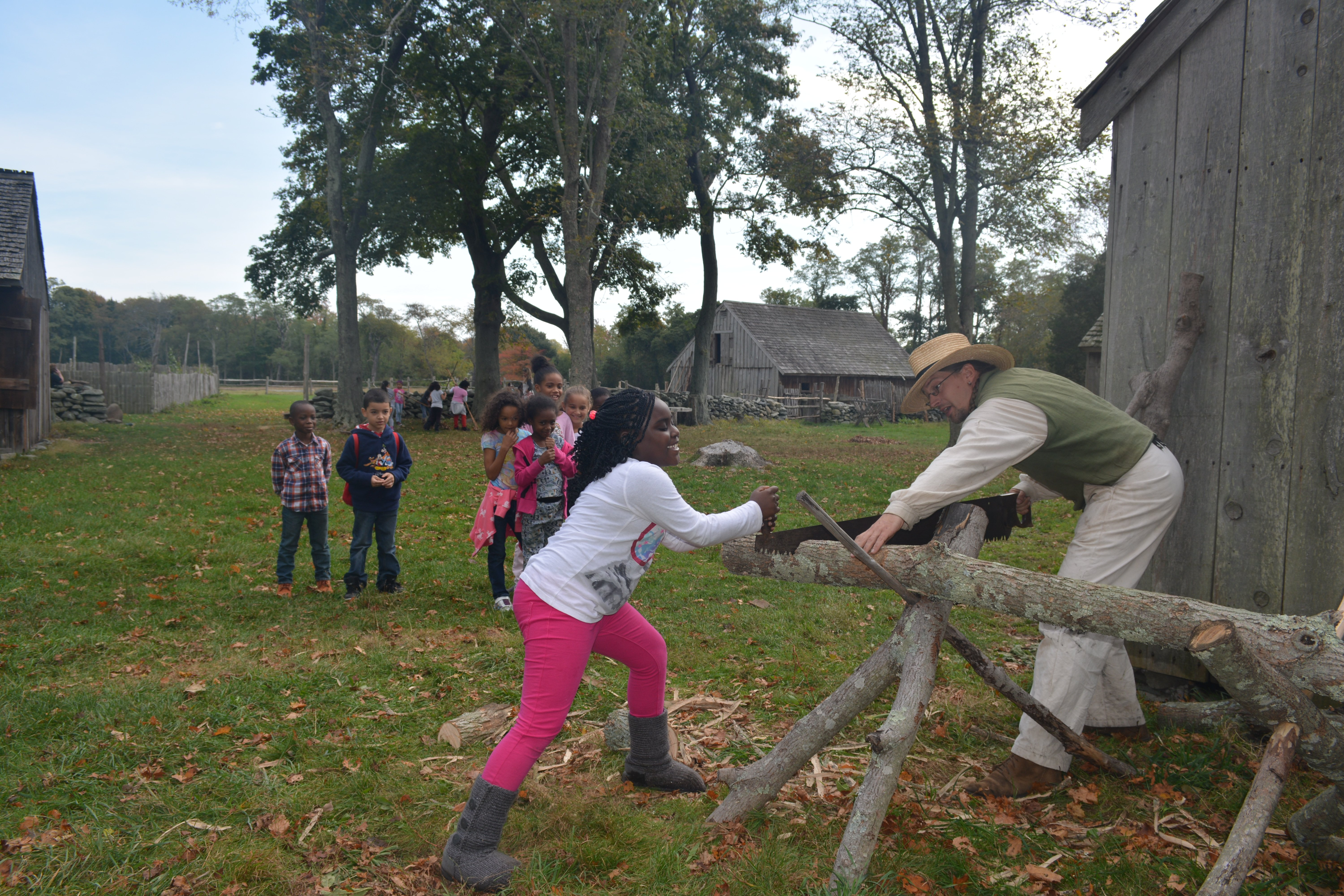 Assistant Director Casey Duckett teaches a child how to use the two-man saw at Coggeshall Farm Museum.